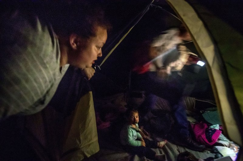 Twenty-month-old Neala Clark sits on the floor of the tent she has been living in with her mother, Mystie Gregory, left, and fiancé, Gary LaPlant, as he loads their personal belongings into a car taking them to a hallway home he found for them in the middle of a rain storm in Youngstown, Fla, Wednesday, Jan. (AP Photo/David Goldman)