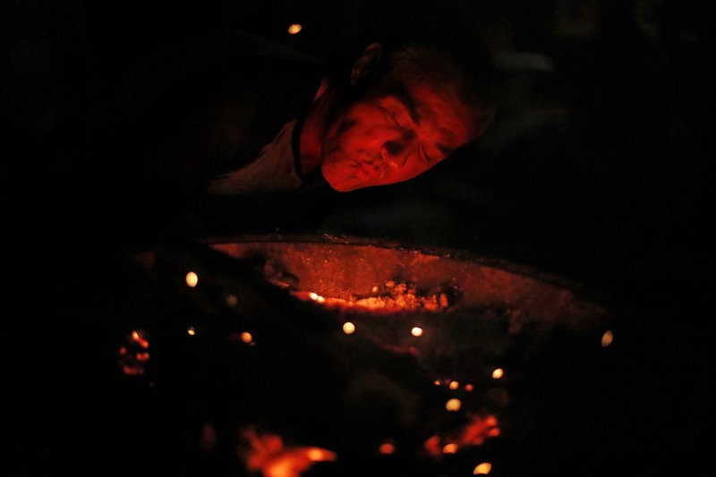 Gene Hogan blows on a campfire outside the tent he's living in since becoming homeless from Hurricane Michael in Youngstown, Fla, Wednesday, Jan. (AP Photo/David Goldman)