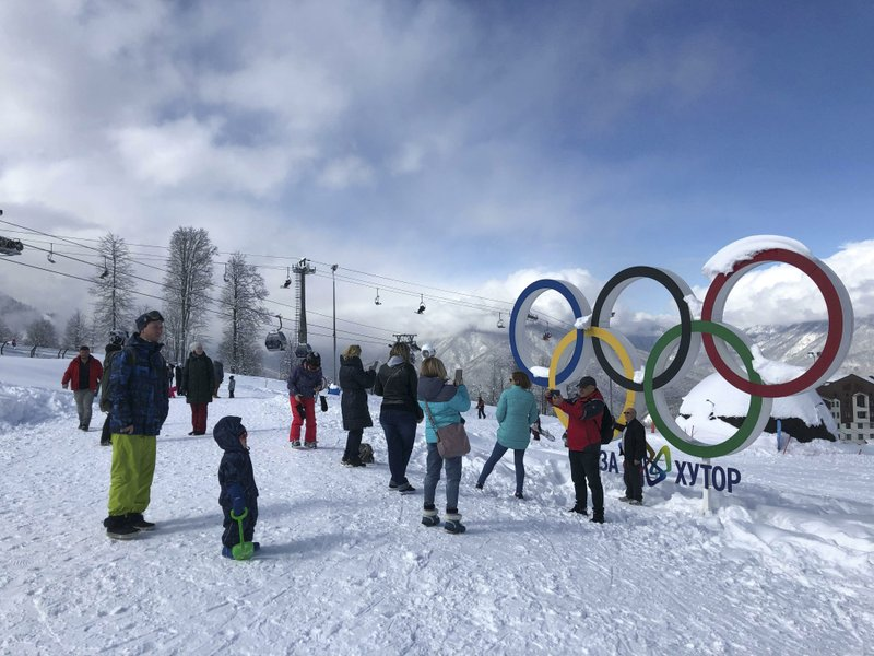 In this photo taken on Sunday, March 3, 2019, tourists walk next to the Olympic rings at the mountain resort of Krasnaya Polyana near the Black Sea resort of Sochi, southern Russia. (AP Photo/James Ellingworth)