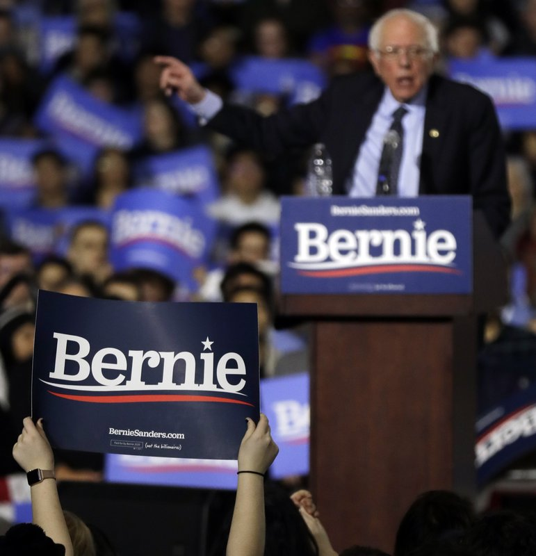 Supporters hold signs as they listen to Sen. Bernie Sanders, I-Vt., where he holds his 2020 presidential campaign at Navy Pier in Chicago, Sunday, March 3, 2019. (AP Photo/Nam Y. Huh)