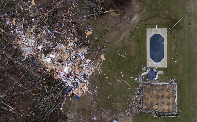 Debris from a home litters a yard the day after a tornado blew it off its foundation, lower right, in Beauregard, Ala. (AP Photo/David Goldman)