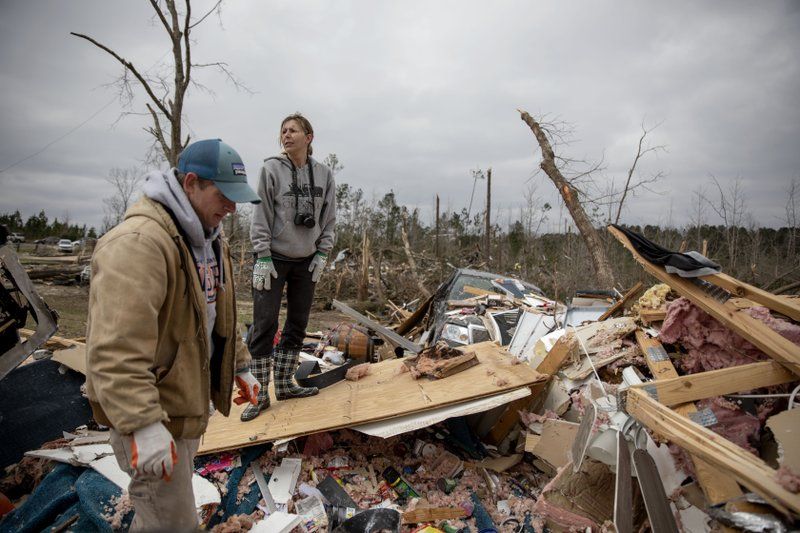 Ashley Griggs, right, helps Joey Roush, left sift through what's left of his mother's home after it was destroyed by a tornado in Beauregard, Ala. (AP Photo/David Goldman)