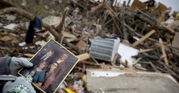 Danny Allen recovers a family photo while sifting through the debris of a friend's home destroyed by a tornado in Beauregard, Ala. (AP Photo/David Goldman)