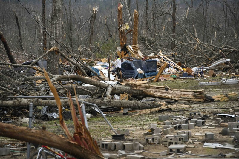 Brittney Downs looks through the debris of a family member's destroyed home the day after a deadly tornado ravaged the area, in Beauregard, Ala. (AP Photo/Julie Bennett)