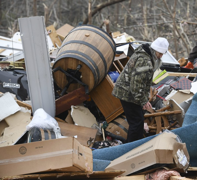 Julie Morrison looks through the debris of her destroyed home on Lee County Road 63 in Beauregard, Ala. (AP Photo/Julie Bennett)