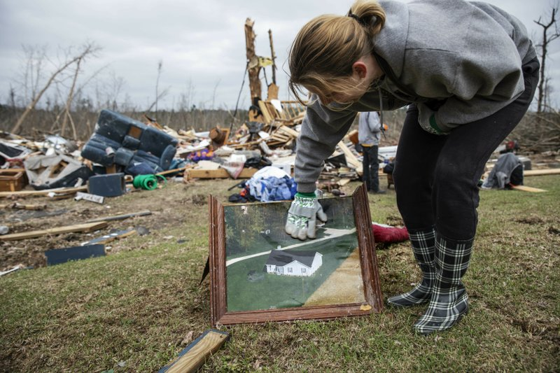 Debris from a friend's home stands in the background as Ashley Griggs wipes away dirt from a photo found in the rubble of what it used to look like before it was destroyed by a tornado in Beauregard, Ala. (AP Photo/David Goldman)
