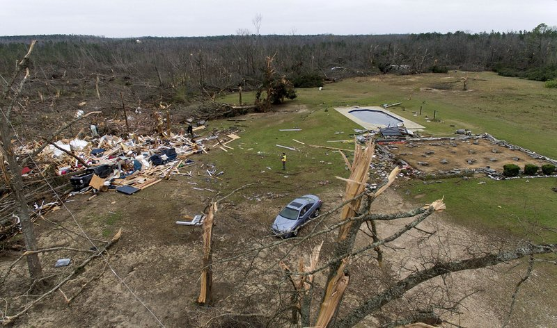Debris from a home litters a yard the day after a tornado blew it off its foundation, at right, in Beauregard, Ala. (AP Photo/David Goldman)