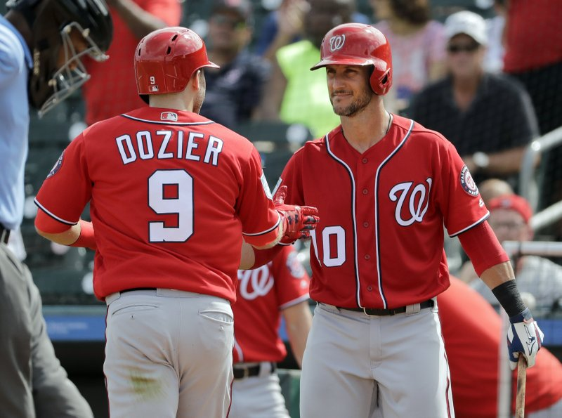 Washington Nationals' Brian Dozier (9) is congratulated by teammate Yan Gomes after hitting a solo home run during the fourth inning of an exhibition spring training baseball game against the Miami Marlins Friday, March 1, 2019, in Jupiter, Fla. (AP Photo/Jeff Roberson)