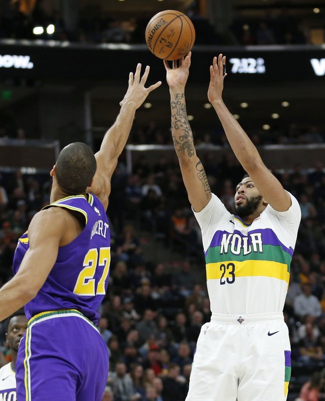 New Orleans Pelicans forward Anthony Davis (23) shoots as Utah Jazz center Rudy Gobert (27) defends in the first half during an NBA basketball game Monday, March 4, 2019, in Salt Lake City. (AP Photo/Rick Bowmer)