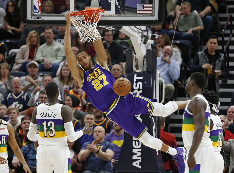 Utah Jazz center Rudy Gobert (27) dunks as New Orleans Pelicans forward Cheick Diallo (13)watches in the first half during an NBA basketball game Monday, March 4, 2019, in Salt Lake City. (AP Photo/Rick Bowmer)