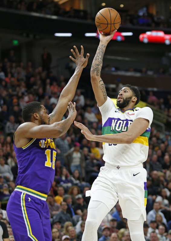 New Orleans Pelicans forward Anthony Davis, right, shoots as Utah Jazz forward Derrick Favors (15) defends in the first half during an NBA basketball game Monday, March 4, 2019, in Salt Lake City. (AP Photo/Rick Bowmer)
