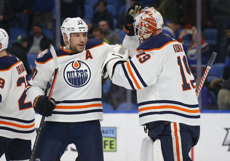 Edmonton Oilers forward Milan Lucic (27) and goalie Mikko Koskinen (19) celebrate a victory following the third period of an NHL hockey game against the Buffalo Sabres, Monday, March 4, 2019, in Buffalo N. (AP Photo/Jeffrey T. Barnes)
