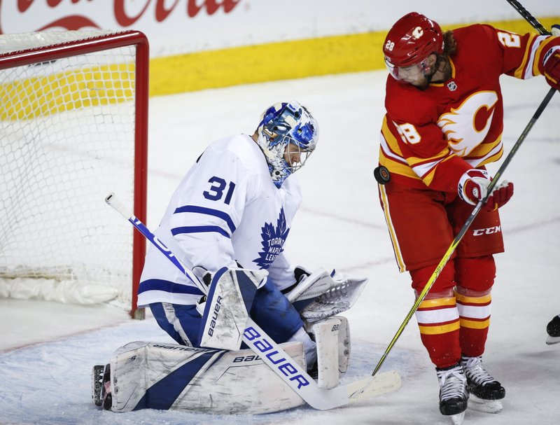 Toronto Maple Leafs goalie Frederik Andersen, left, of Denmark, blocks the net on Calgary Flames' Elias Lindholm, of Sweden, during first period NHL hockey action in Calgary, Alberta, Monday, March 4, 2019. (Jeff McIntosh/The Canadian Press via AP)