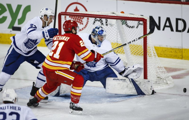 Toronto Maple Leafs goalie Frederik Andersen, right, of Denmark, deflects a shot from Calgary Flames' Garnet Hathaway, center, as Martin Marincin, of Slovakia, looks on during second-period NHL hockey action in Calgary, Alberta, Monday, March 4, 2019. (Jeff McIntosh/The Canadian Press via AP)