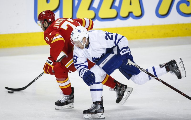 Toronto Maple Leafs' Connor Brown, right, chases Calgary Flames' Mark Jankowski during first period NHL hockey action in Calgary, Alberta, Monday, March 4, 2019. (Jeff McIntosh/The Canadian Press via AP)