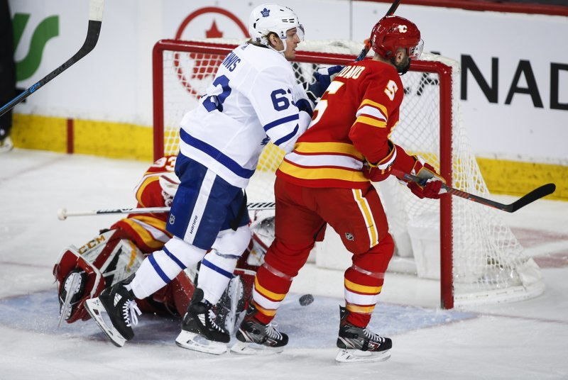 Toronto Maple Leafs' Tyler Ennis, centre, scores on Calgary Flames goalie David Rittich, left, of the Czech Republic, as Mark Giordano looks on during first period NHL hockey action in Calgary, Alberta, Monday, March 4, 2019. (Jeff McIntosh/The Canadian Press via AP)