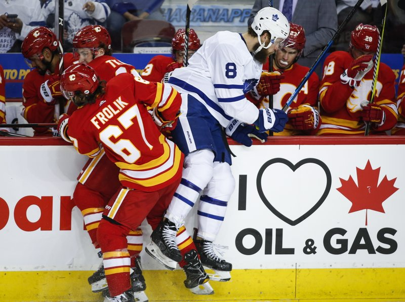 Toronto Maple Leafs' Jake Muzzin, right, is checked by Calgary Flames' Michael Frolik, front left, of the Czech Republic, and Matthew Tkachuk during second-period NHL hockey action in Calgary, Alberta, Monday, March 4, 2019. (Jeff McIntosh/The Canadian Press via AP)