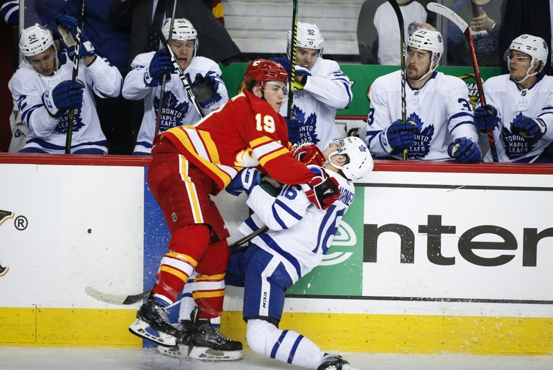 Toronto Maple Leafs' Mitch Marner, right, is checked by Calgary Flames' Matthew Tkachuk during first period NHL hockey action in Calgary, Alberta, Monday, March 4, 2019. (Jeff McIntosh/The Canadian Press via AP)