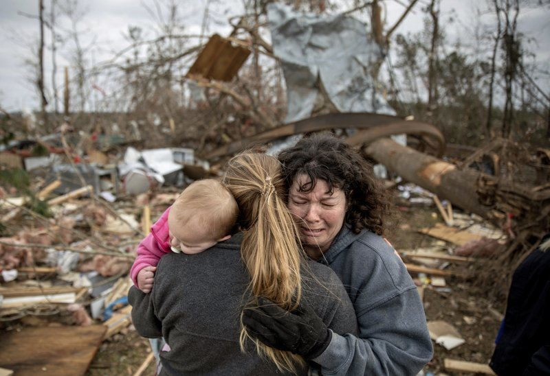 Carol Dean, right, cries while embraced by Megan Anderson and her 18-month-old daughter Madilyn, as Dean sifts through the debris of the home she shared with her husband, David Wayne Dean, who died when a tornado destroyed the house in Beauregard, Ala. (AP Photo/David Goldman)