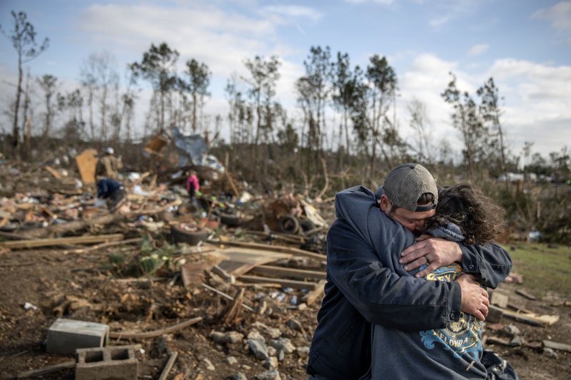 ADDED SHARED WITH-Carol Dean, right, is embraced by David Theo Dean as they sift through the debris of the home Carol shared with her husband and David's father, David Wayne Dean, who died when a tornado destroyed the house in Beauregard, Ala. (AP Photo/David Goldman)