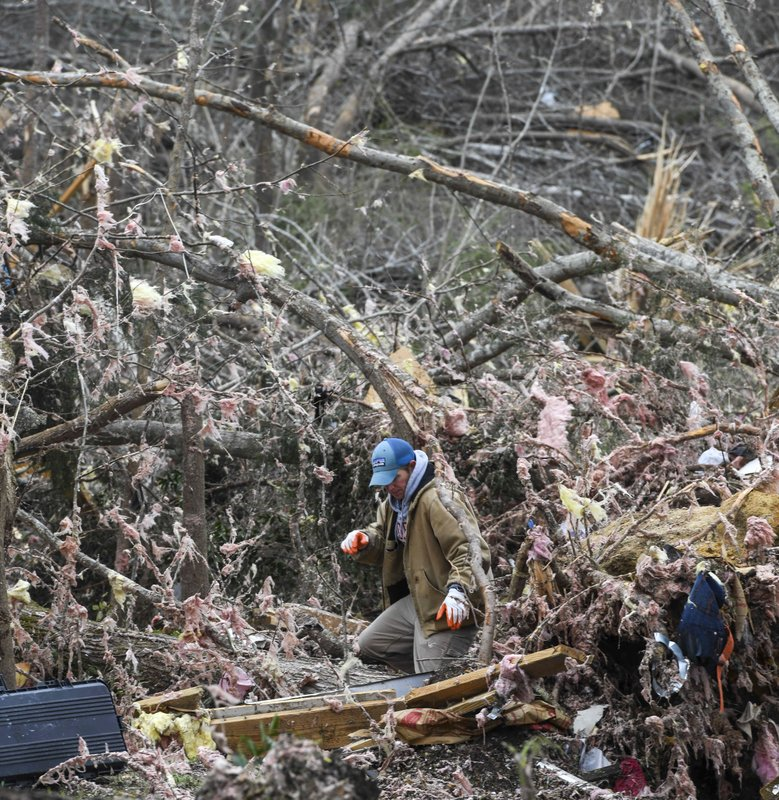 A resident looks through the debris of a family member's destroyed home the day after a deadly tornado ravaged the area, in Beauregard, Ala. (AP Photo/Julie Bennett)