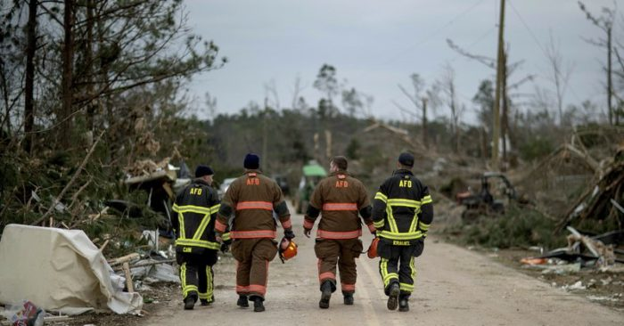 First responders walk through a neighborhood heavily damaged by a tornado a day earlier in Beauregard, Ala. (AP Photo/David Goldman)