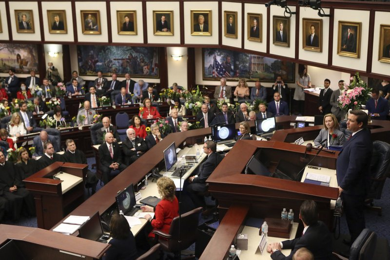 Florida Gov.  Ron DeSantis, right, gives the state of the state address on the first day of legislative session Tuesday, March 5, 2019, in Tallahassee, Fla. (AP Photo/Steve Cannon)