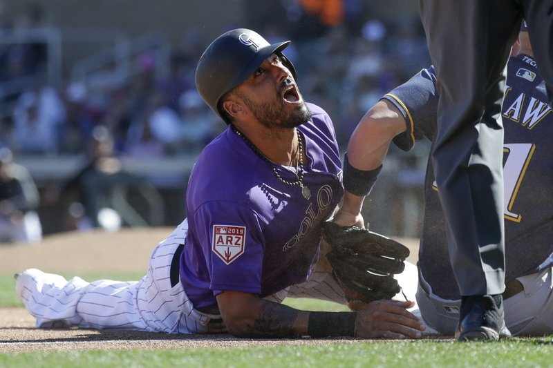 Colorado Rockies first baseman Ian Desmond reacts after getting tagged out stealing third by Milwaukee Brewers third baseman Travis Shaw during the fourth inning of a spring baseball game in Scottsdale, Ariz. (AP Photo/Chris Carlson)