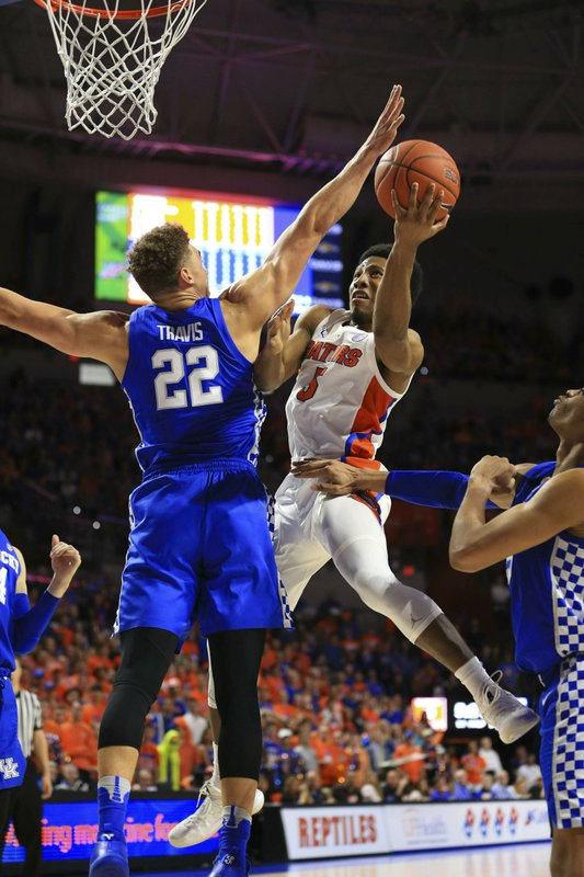 FILE - In this Saturday, Feb. 2, 2019, file photo, Florida guard KeVaughn Allen scores over Kentucky forward Reid Travis during the first half of an NCAA college basketball game in Gainesville, Fla. (AP Photo/Matt Stamey, File)