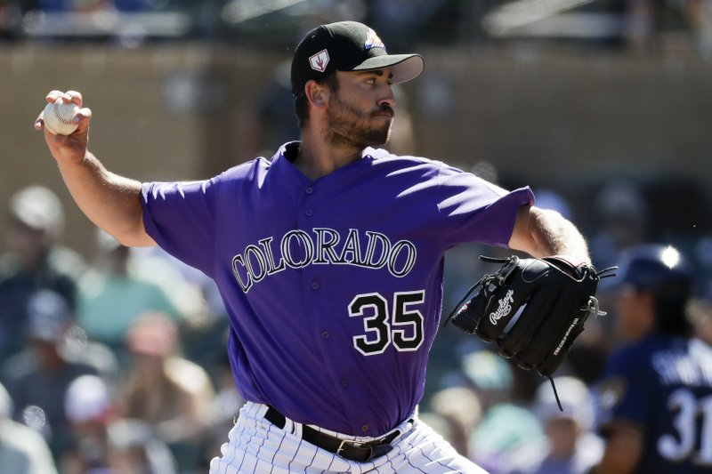Colorado Rockies starting pitcher Chad Bettis throws to a Milwaukee Brewers batter during the first inning of a spring baseball game in Scottsdale, Ariz. (AP Photo/Chris Carlson)
