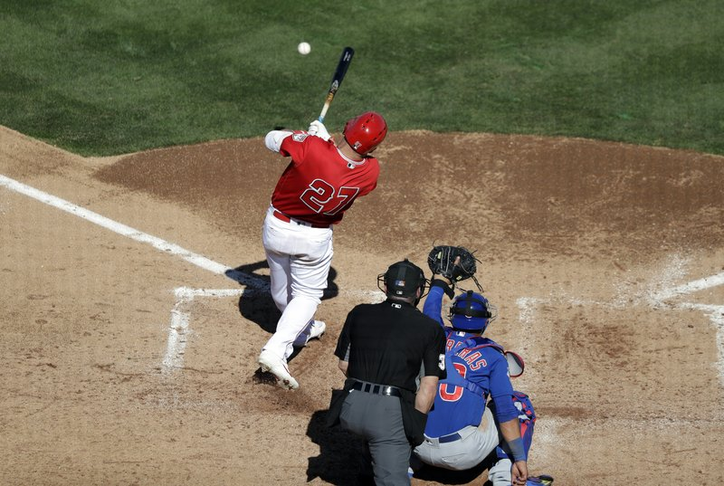 Los Angeles Angels' Mike Trout (27) singles as Chicago Cubs catcher Willson Contreras and the home plate umpire look on in the fifth inning of a spring training baseball game Tuesday, March 5, 2019, in Tempe, Ariz. (AP Photo/Elaine Thompson)