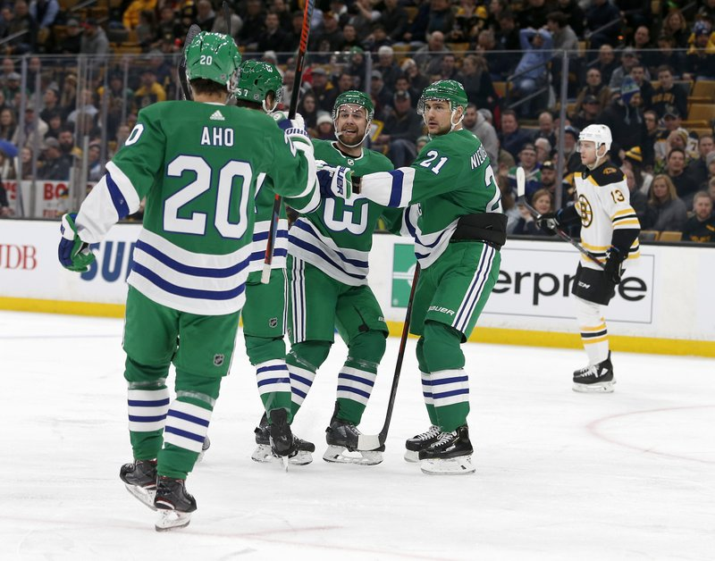Carolina Hurricanes defenseman Calvin de Haan, center, celebrates with teammates after scoring a goal during the first period of an NHL hockey game against the Boston Bruins, Tuesday, March 5, 2019, in Boston. (AP Photo/Mary Schwalm)