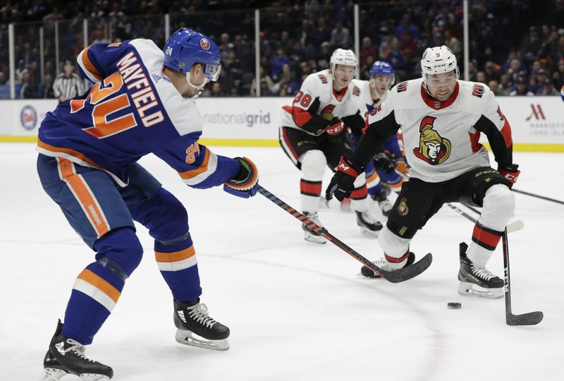 New York Islanders defenseman Scott Mayfield (24) shoots with Ottawa Senators defenseman Cody Ceci (5) defending during the second period of an NHL hockey game Tuesday, March 5, 2019, in Uniondale, N. (AP Photo/Kathy Willens)