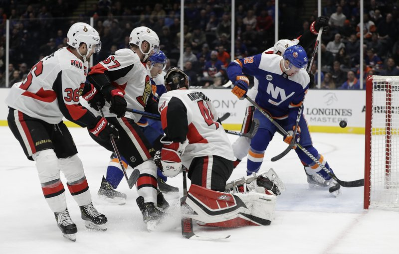 New York Islanders left wing Ross Johnston (32) flicks the puck in the crease behind Ottawa Senators goaltender Craig Anderson (41) with Senators center Colin White (36) and defenseman Ben Harpur (67) watching during the second period of an NHL hockey game Tuesday, March 5, 2019, in Uniondale, N. (AP Photo/Kathy Willens)