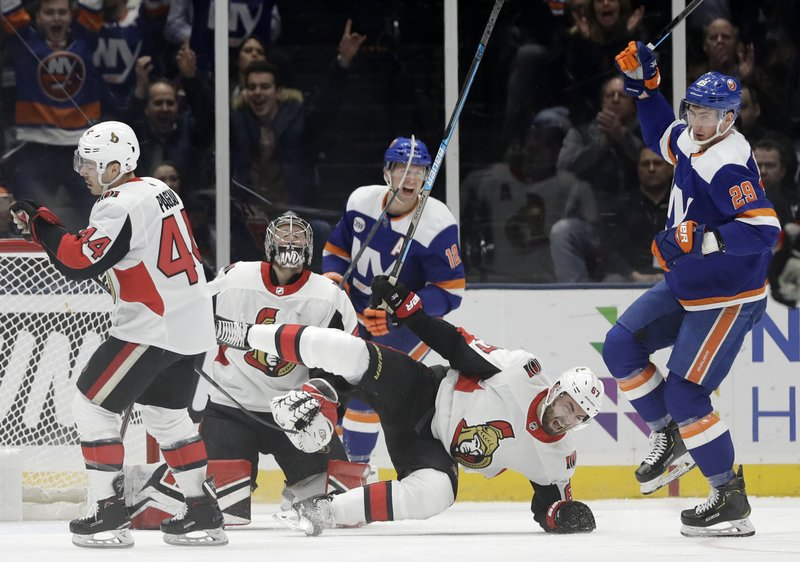 New York Islanders right wing Josh Bailey (12), who assisted, and center Brock Nelson (29) celebrate Nelson's goal as Ottawa Senators center Jean-Gabriel Pageau (44) and goaltender Craig Anderson react while Senators defenseman Ben Harpur falls during the first period of an NHL hockey game, Tuesday, March 5, 2019, in Uniondale, N. (AP Photo/Kathy Willens)