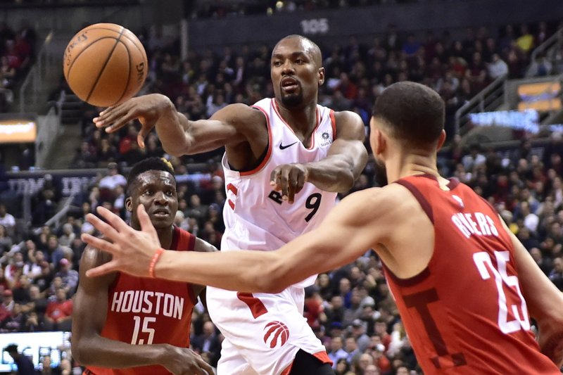 Toronto Raptors center Serge Ibaka (9) dishes off a pass as Houston Rockets guard Austin Rivers (25) defends during the first half of an NBA basketball game Tuesday, March 5, 2019, in Toronto. (Frank Gunn/The Canadian Press via AP)