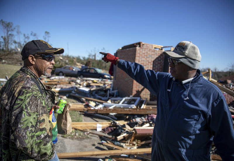 Dexter Norwood, left, and Bernard Reese talk about the people they found in the rubble immediately following a tornado that devastated their neighborhood in Beauregard, Ala. (AP Photo/David Goldman)