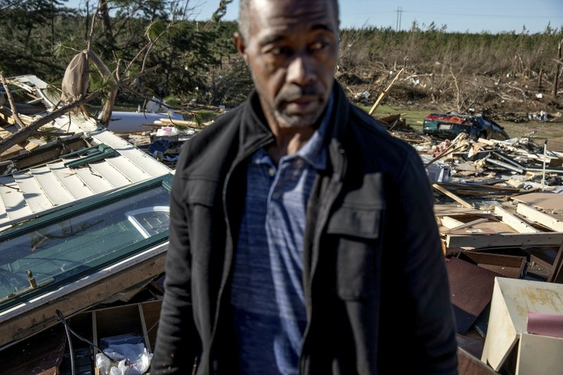 Richard Tate stands amid what's left of his home where he survived a tornado with his wife Tuesday, March 5, 2019 in Beauregard, Ala. (AP Photo/David Goldman)