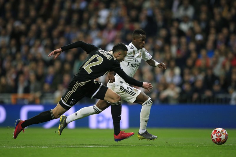 Ajax's Noussair Mazraoui, left, tries to stop Real forward Vinicius Junior during the Champions League round of 16 second leg soccer match soccer match between Real Madrid and Ajax at the Santiago Bernabeu stadium in Madrid, Tuesday, March 5, 2019. (AP Photo/Bernat Armangue)
