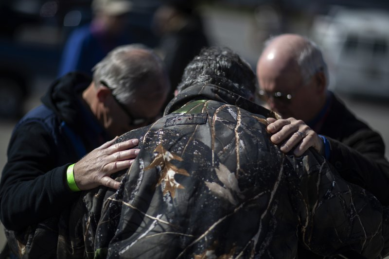 Rand Bowman, left, prays with fellow volunteers, Paul Kelley, center, and Bruce Button outside a donation distribution site in Opelika, Ala. (AP Photo/David Goldman)