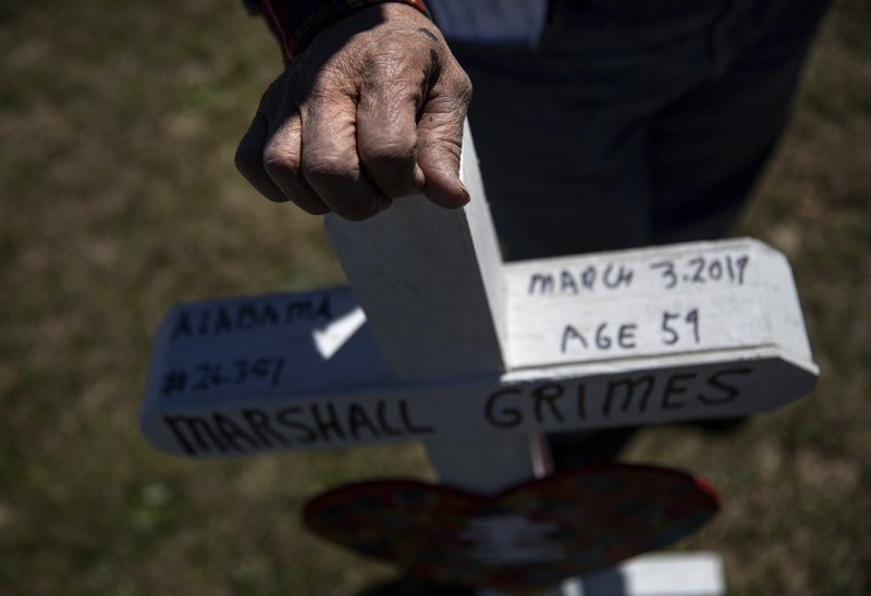 Greg Zanis rests his hand on one of the crosses he made for each victim of Sunday's tornado after placing them as a makeshift memorial in Opelika, Ala. (AP Photo/David Goldman)
