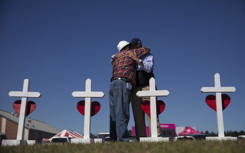 Rev. Arthur Thomas, right, of Mt. Nebo Baptist Church, right, is embraced by Greg Zanis who built a cross for each victim of the tornado and placed them as a makeshift memorial in Beauregard, Ala. (AP Photo/David Goldman)