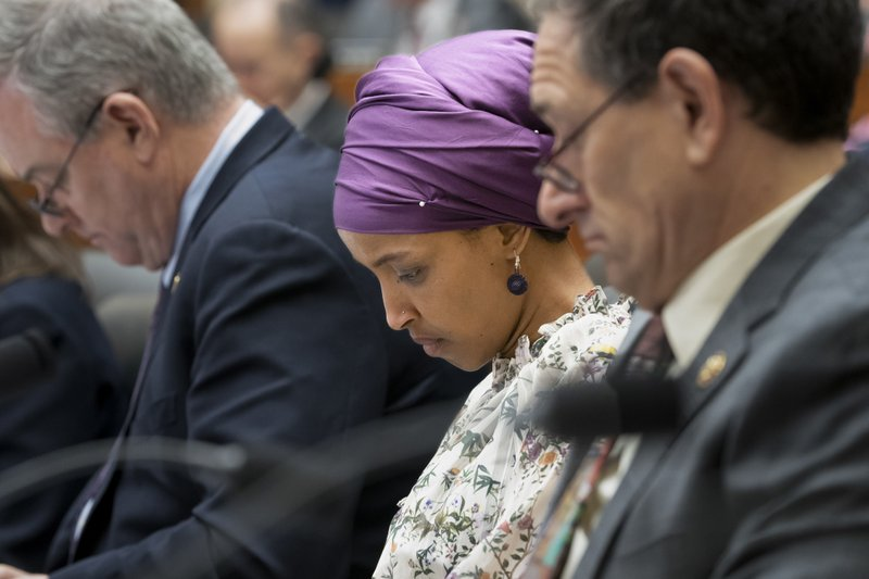 Rep. Ilhan Omar, D-Minn., sits with fellow Democrats, Rep. David Trone, D-Md., left, and Rep. Mike Levin, D-Calif. (AP Photo/J. Scott Applewhite)