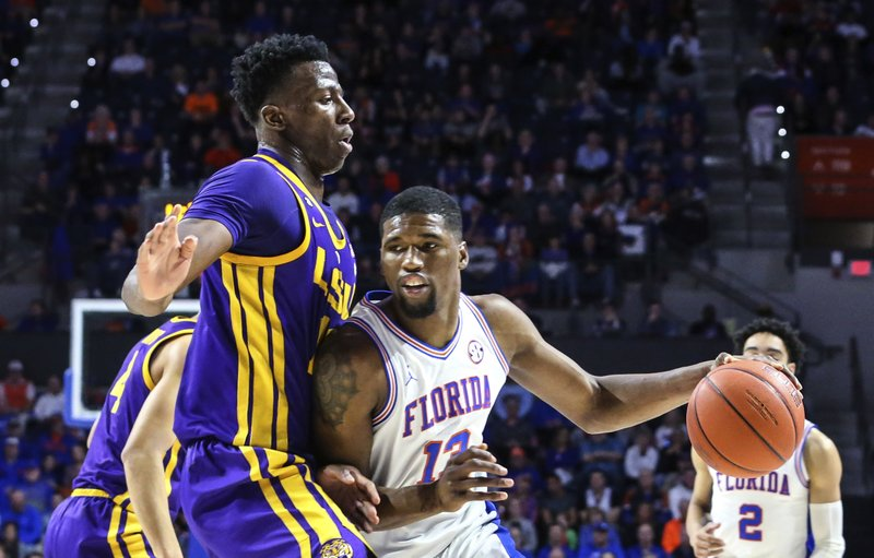 Florida center Kevarrius Hayes (13) is defended by LSU forward Kavell Bigby-Williams, left, during the first half of an NCAA college basketball game in Gainesville, Fla. (AP Photo/Gary McCullough)