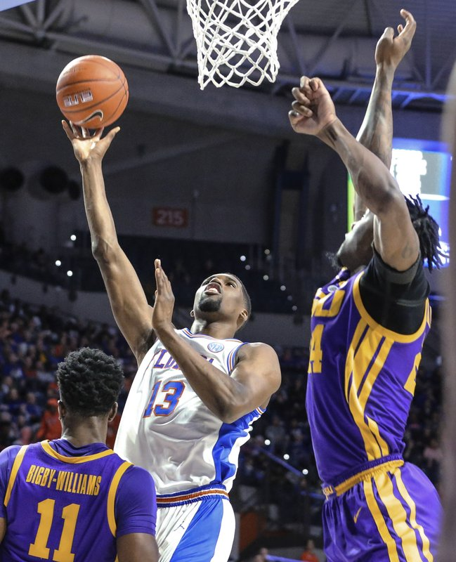 Florida center Kevarrius Hayes (13) shoots while defended by LSU forward Emmitt Williams, right, during the first half of an NCAA college basketball game in Gainesville, Fla. (AP Photo/Gary McCullough)