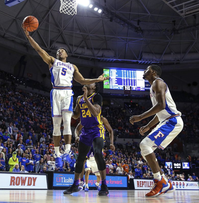 Florida guard KeVaughn Allen (5) gathers in an offensive rebound in front of LSU forward Emmitt Williams (24) during the first half of an NCAA college basketball game in Gainesville, Fla. (AP Photo/Gary McCullough)