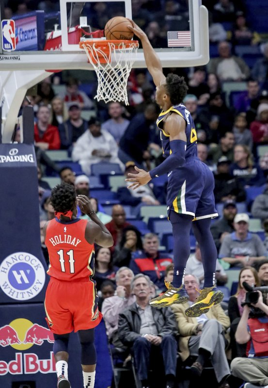Utah Jazz guard Donovan Mitchell (45) finishes a steal with a dunk on New Orleans Pelicans guard Jrue Holiday (11) in the first half of an NBA basketball game in New Orleans, Wednesday, March 6, 2019. (AP Photo/Scott Threlkeld)