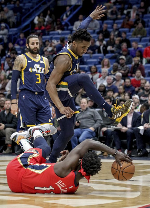 Utah Jazz guard Donovan Mitchell (45) fouls New Orleans Pelicans guard Jrue Holiday (11) on a drive in the first half of an NBA basketball game in New Orleans, Wednesday, March 6, 2019. (AP Photo/Scott Threlkeld)