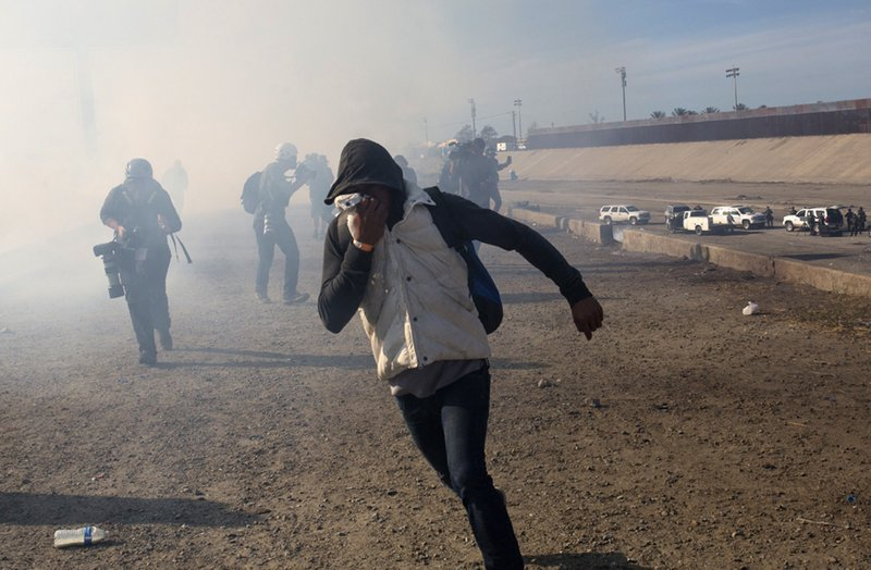 FILE - In this Nov. 25, 2018 file photo, a migrant runs from tear gas launched by U.S. agents, amid members of the press covering the Mexico-U. (AP Photo/Rodrigo Abd, File)