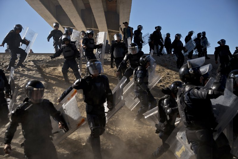 FILE - In this Nov. 25, 2018 file photo, Mexican police run as they try to keep migrants from getting past the Chaparral border crossing in Tijuana, Mexico, near San Ysidro, Calif. (AP Photo/Ramon Espinosa, File)